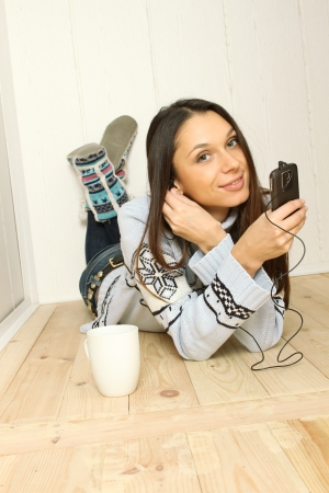 Woman lying on the floor at home listening to the radio photo