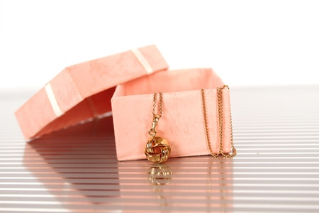 women s fashion: Close-up of a gold chain with a pendant in a gift box Stock Photo