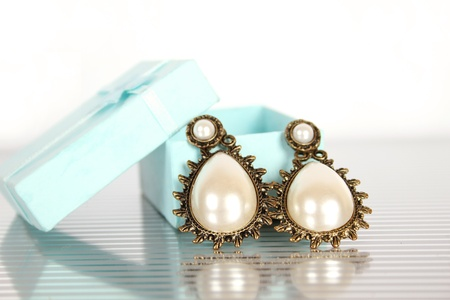 Close-up of big earrings with pearls in a gift box