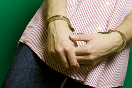 Caucasian man in a striped shirt on a green background hands handcuffed photo
