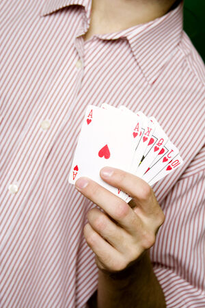A young man in a red striped shirt, holding Royal flush photo