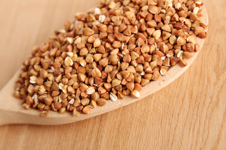 Close-up of buckwheat grains lie in a wooden spoon photo