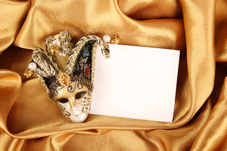 Carnival mask lying on a yellow silk and a sheet of white paper photo
