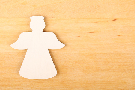 Wooden angel and next word angel on a wooden background Stock Photo