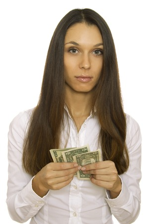 lack of confidence: Close-up of an attractive young business woman holding dollars. Isolated on white background