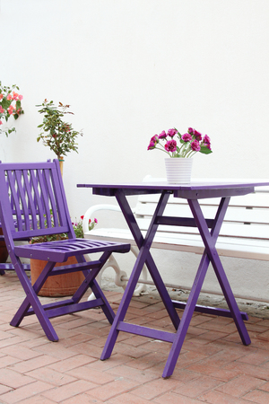 patio chairs: Violet wooden chairs and a table with a bouquet of flowers