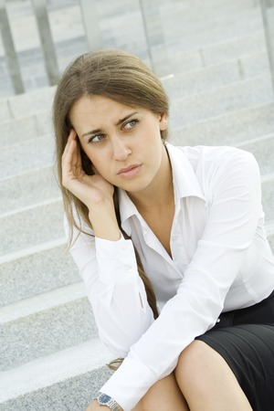 Young business woman tormented by headaches cares about the work