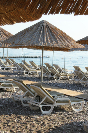 Rocky Beach with sun beds and umbrellas Stock Photo