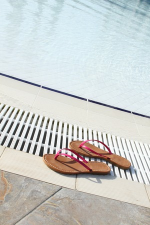 swimming shoes: The swimming pool is outdoors. The pool beach shoes