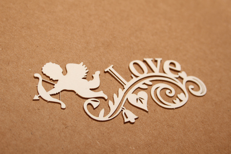 Love wooden letters on the background of the little hearts and angel.