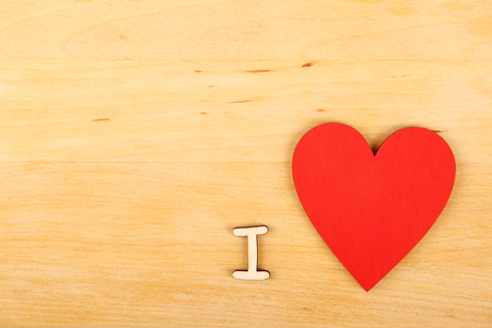 Wooden red heart and the text I love you on a wooden background Banco de Imagens