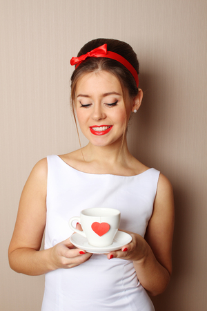 Close up young woman with a cup, which shows a red heart 免版税图像