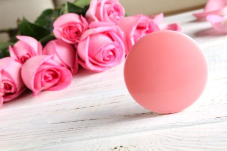 Pot avec de la crème, des roses sur un fond en bois blanc. L'affiche est rose.