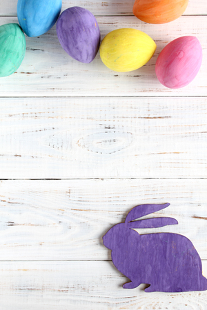 Easter bunny and colored eggs. Wooden lilouet. Background