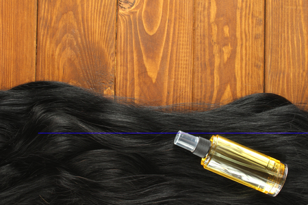 Healthy black hair and a bottle of hair oil Imagens
