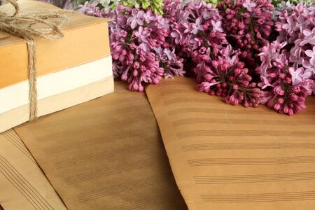 Old clean sheet music, books and lilac flowers Stock Photo