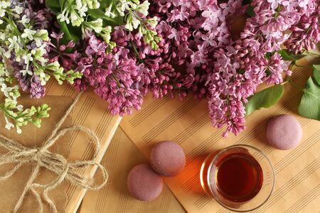 Tea with macaroons on the background of sheet music and lilac flowers
