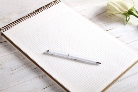 A large notebook with a white pen and a beautiful white rose. Standard-Bild - 133908781