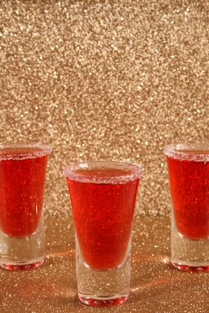 Three glasses with red alcoholic drinks. Background gold shiny