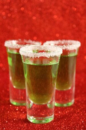 Two glasses with a green drink. Background from red spangles. Reklamní fotografie