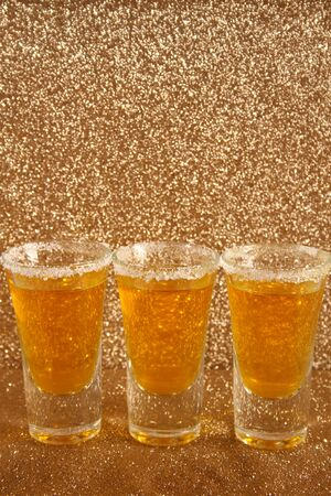 Glasses with a yellow drink. Background from gold spangles.