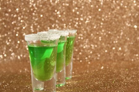 Glasses with a green drink. Background from gold spangles.
