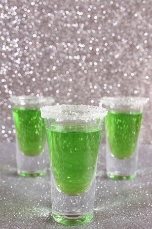 Three glasses with green alcoholic drinks. Background silver shiny