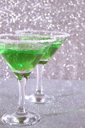 Two glasses with green alcoholic drinks. Background silver shiny 写真素材