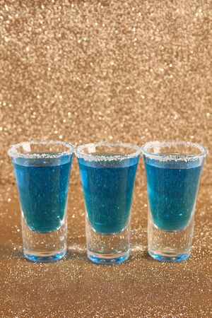 Three glasses with blue alcoholic drinks. Stand on a gold shiny background.