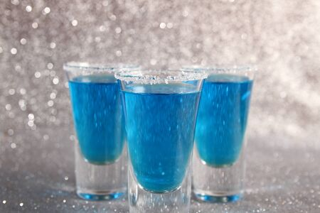 Three glasses with blue alcoholic drinks. Stand on a silver shiny background.