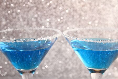 Two glasses with blue alcoholic drinks. Stand on a silver shiny background.