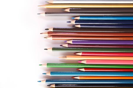 Many multi-colored pencils lie in a row on a white background