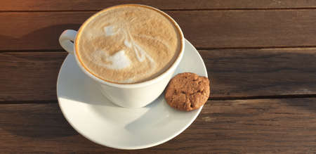Cup of aromatic cappuccino and cookies on a wooden table. The street