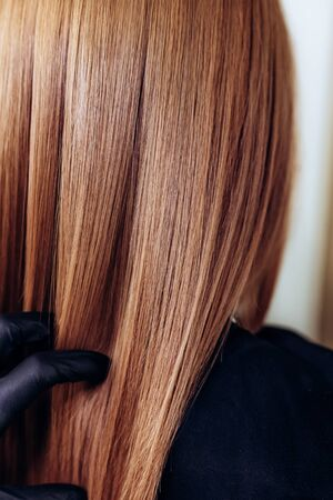 Professional hairdresser brushing straight clients redhead hair after hair care beauty procedures.Vertical