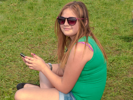 Teenage girl sitting in the midst of a green glade with a mobile phone in hand. Female child a little overweight, sunglasses, summer sunny day.