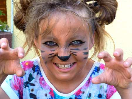 Growl child painted black pencil under the feline animal. Hands crouched near the face. photo