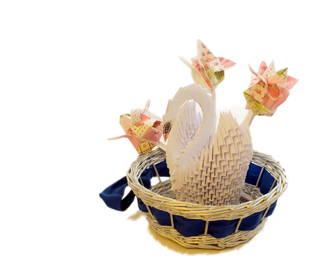 a place for the text: Paper floristry, white swan of the paper modules in the blue basket with three tulips of napkins on white background, there is a place for text