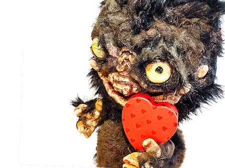 Muzzle monster with fangs, bulging eyes and a huge mouth toy fur and papier mache, the beast faces hearts