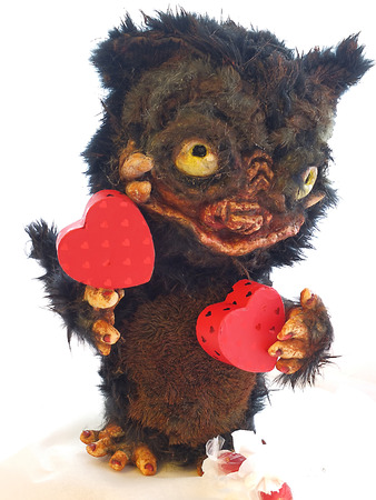 bacteria in heart: Muzzle monster with fangs, bulging eyes and a huge mouth toy fur and papier mache, the beast faces hearts