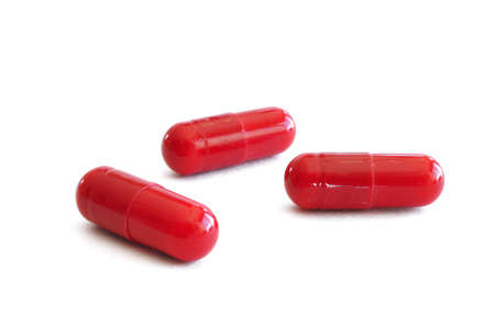Three Red Pills (Capsules) Isolated on a White Background