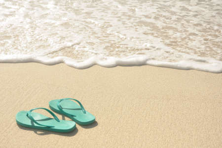 flip flops: Green Flip Flops on a Sandy Beach Stock Photo