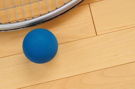racquetball: Racquetball de goma azul y raqueta en el piso de madera dura Corte Foto de archivo
