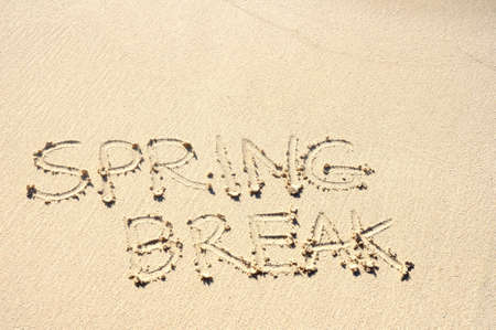 spring message: The Words Spring Break Written in the Sand on a Beach