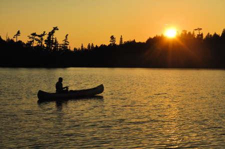 Een man vissen vanuit een kano bij zonsondergang op een afgelegen wildernis Lake Stockfoto