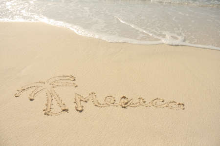 The Word Mexico and a Palm Tree Drawn in Sand on Beach photo