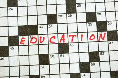 word game: The Word Education on Crossword Puzzle in Red Ink, Copy Space Stock Photo
