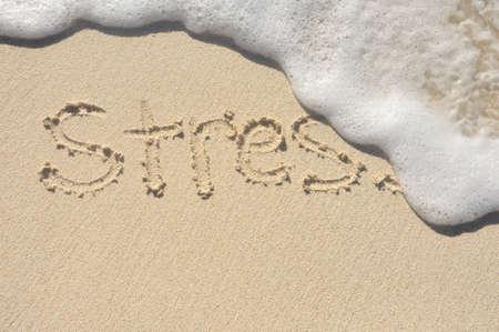 Alleviare lo stress, la parola stress essere spazzata via da un'onda sulla spiaggia Archivio Fotografico