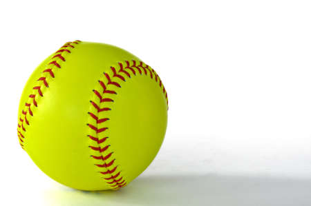 Yellow softball with red stiching isolated on white  photo
