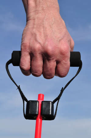 stretchy: Hand Pulling a Resistance Band Against a Blue Sky