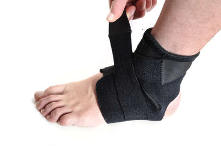 Wrapping a Black Ankle Brace Isolated on White photo